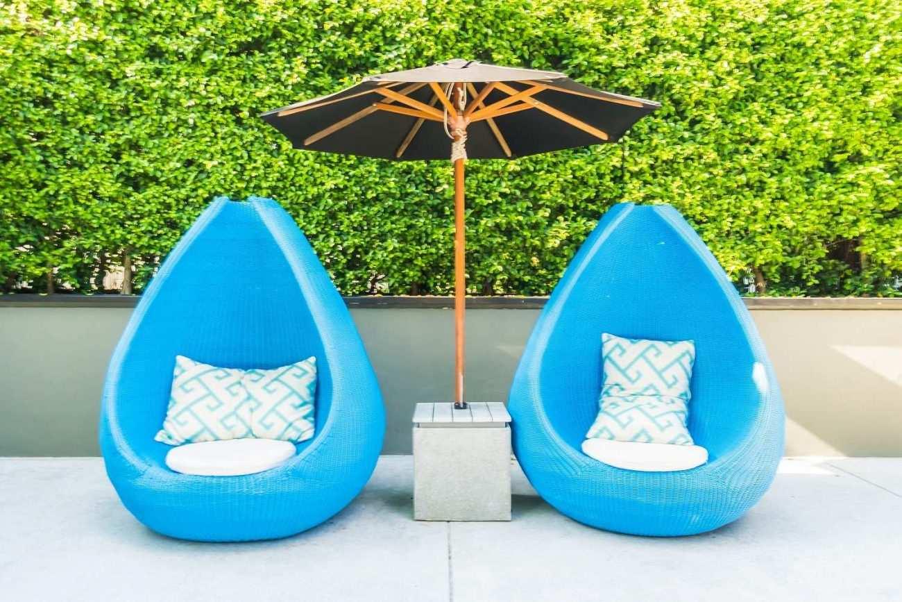 Mavi koltuklar ve şemsiye ile yapılmış Bahçe Mobilyaları Ve Bahçe Dekorasyonu